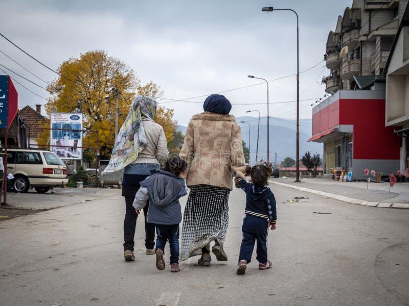 Två flyktingkvinnor och deras döttrar på deras väg att registrera och skriva in Serbien på gränsen med Makedonien på den Balkans  fotografering för bildbyråer