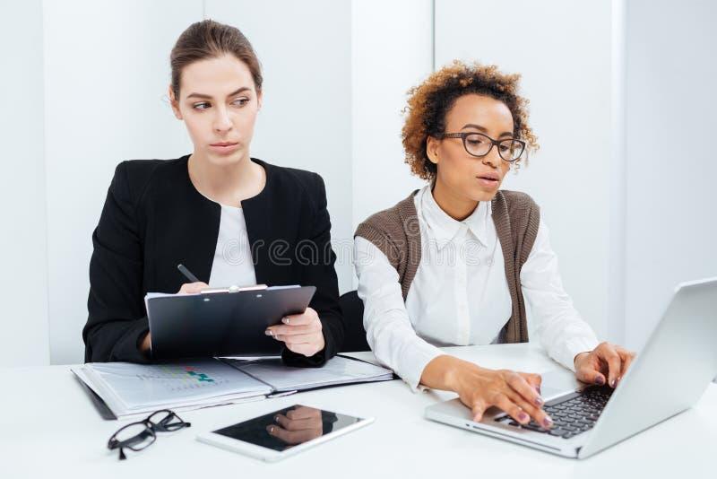 Två fokuserade affärskvinnor som arbetar genom att använda skrivplattan och bärbara datorn arkivbilder