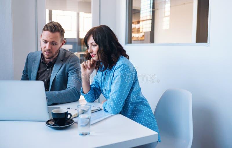 Två fokuserade businesspeople som arbetar på en bärbar dator i ett kontor royaltyfria foton