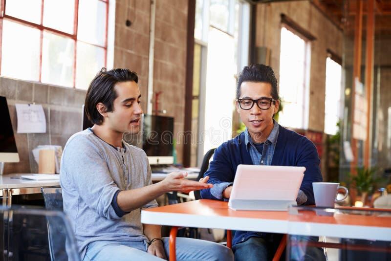 Två formgivare Sit At Meeting Table Working på den Digital minnestavlan royaltyfria foton