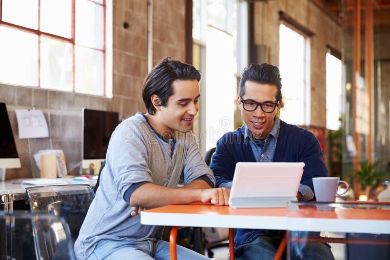 Två formgivare Sit At Meeting Table Working på den Digital minnestavlan royaltyfri bild