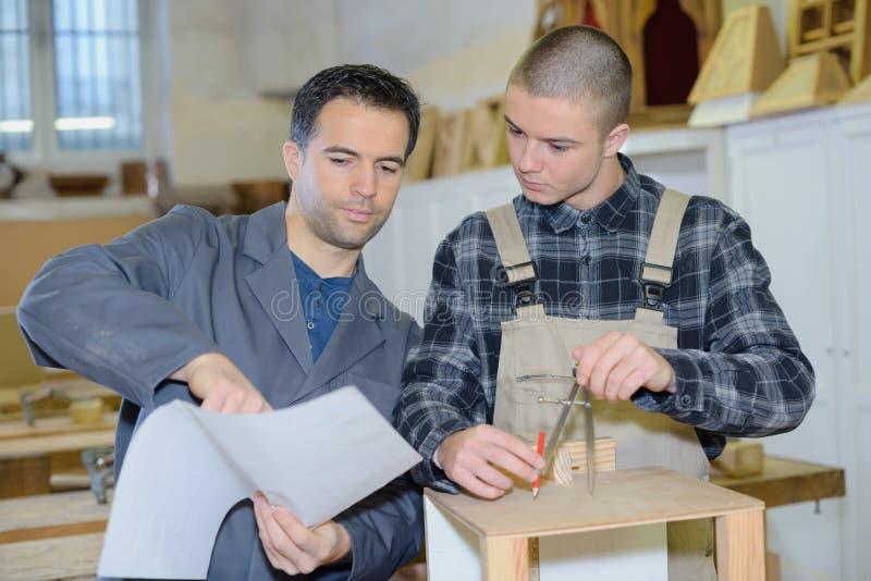 Två formgivare som tillsammans arbetar i seminarium med precisionhjälpmedel arkivfoto