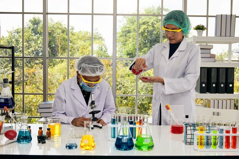 Två forskare forskar det nya kemiska objektet i laboratorium royaltyfri fotografi