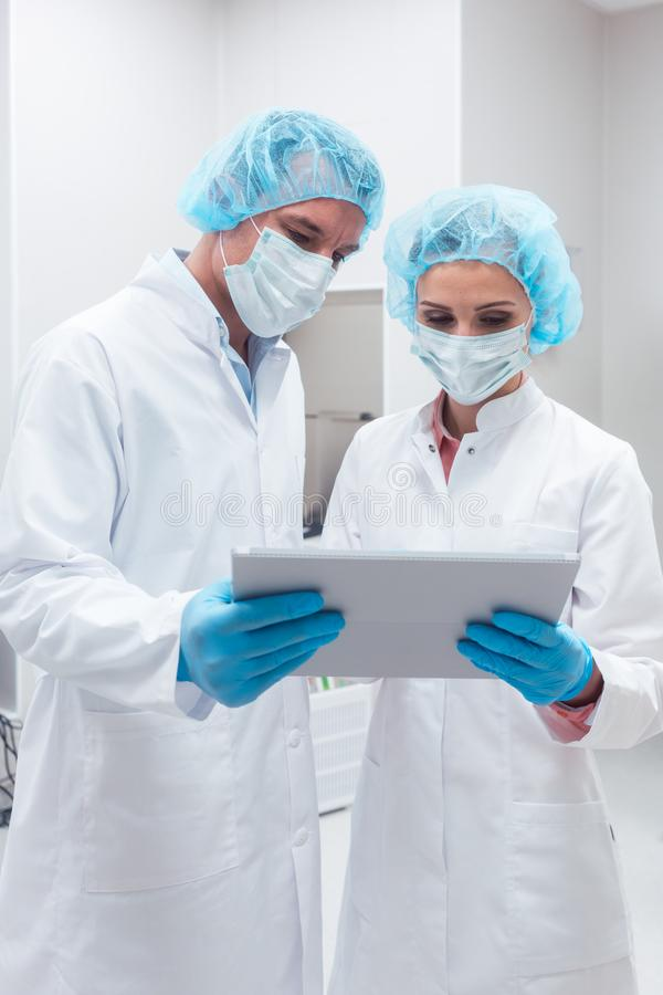 Två forskare som tillsammans arbetar i labbet som ser data royaltyfri foto