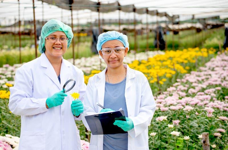 Två forskarekvinnor med ställningen för labbkappa- och hårräkning framme av mång--färg blommor De ler också med begreppet av royaltyfri bild