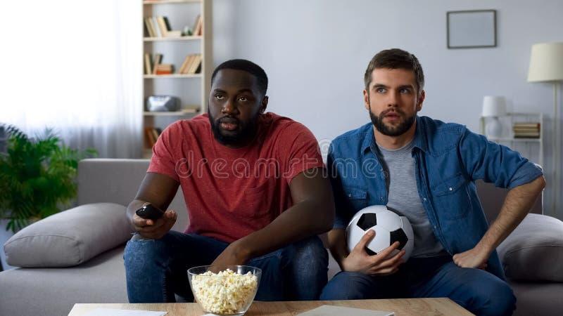 Två fotbollfans som håller ögonen på den amerikanska fotbollsmatchen som försöker att förstå regler royaltyfria bilder
