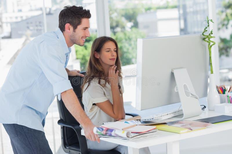Två fotoredaktörer som arbetar på deras dator fotografering för bildbyråer