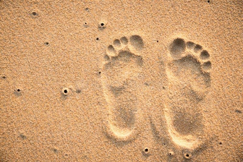 Två fotspår på sandstranden royaltyfria bilder