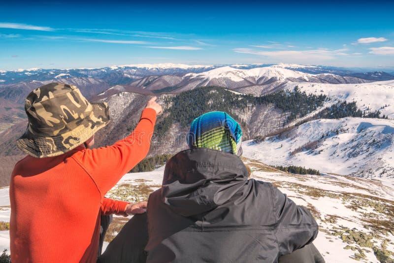 Två fotvandrare på en kulle tycker om dalen med bergmaxima arkivfoton