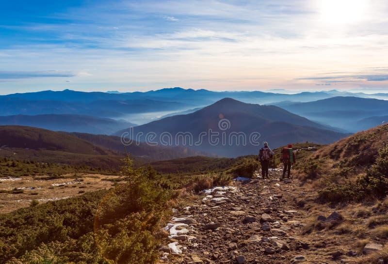 Två fotvandrare som går på bakgrund för berg för bergbanasolnedgång royaltyfri bild