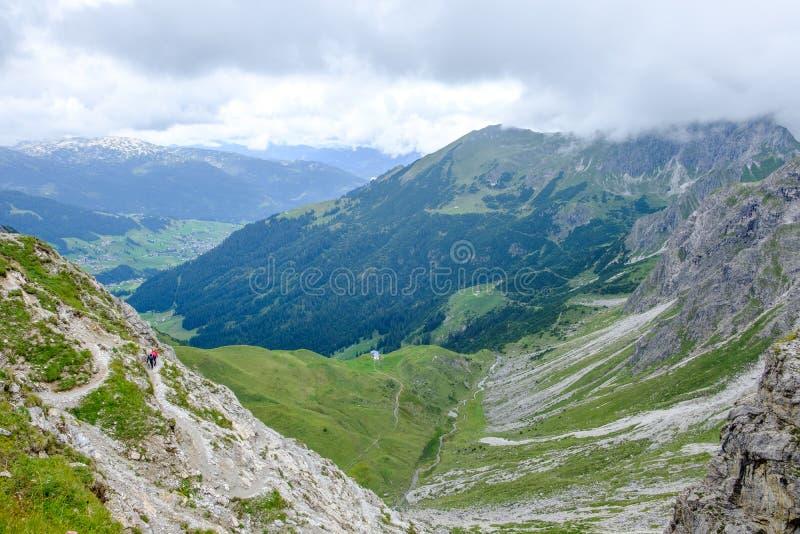 Två fotvandrare som stiger ned in i en dal i de Allgaeu moutainsna på en molnig dag, Österrike arkivfoto
