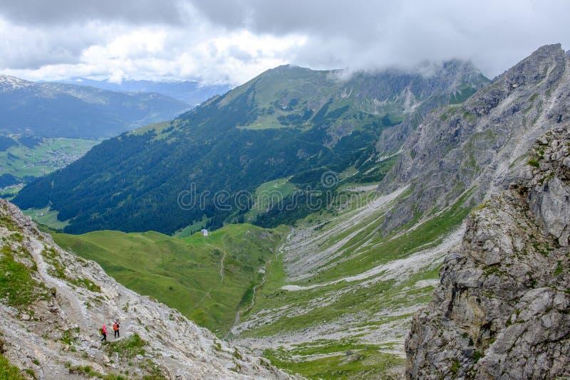 Två fotvandrare som stiger ned in i en dal i de Allgaeu moutainsna på en molnig dag, Österrike arkivfoton