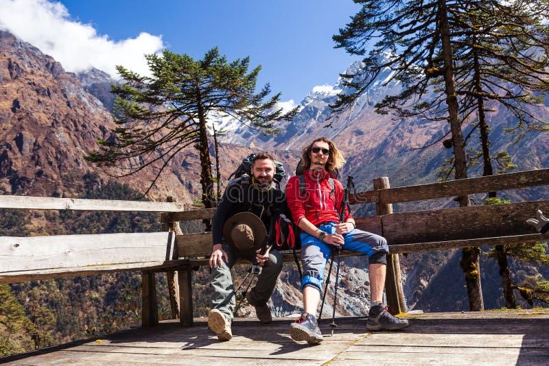 Två fotvandrare som vilar på bergskyddsammanträde på den Wood bänken arkivbild