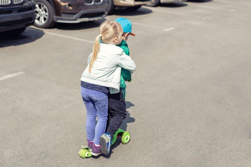 Två frineds pojke och flicka som har gyckel som tillsammans rider en sparkcykel samtidigt Barn som spelar på bilen som parkerar v arkivbild