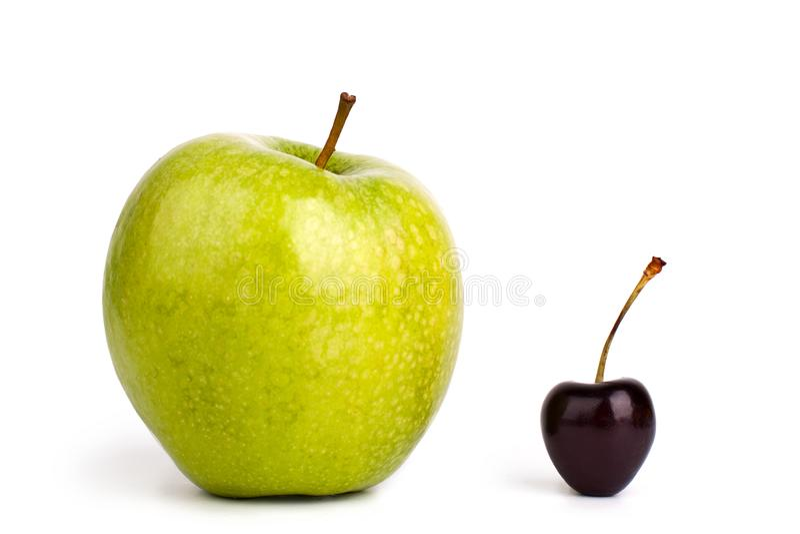 Två frukter ett rött körsbärsrött bär och ett stort grönt äpple på vit bakgrund isolerat slut upp makro arkivbilder