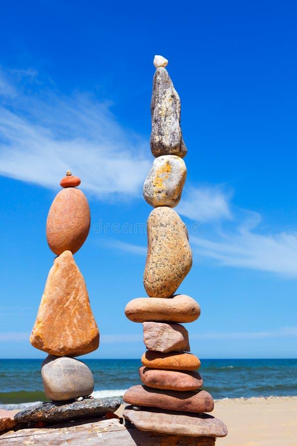 Två frysta pyramider av färggranulat på en strand mot havets bakgrund Begreppet balans, harmoni och meditation royaltyfri foto