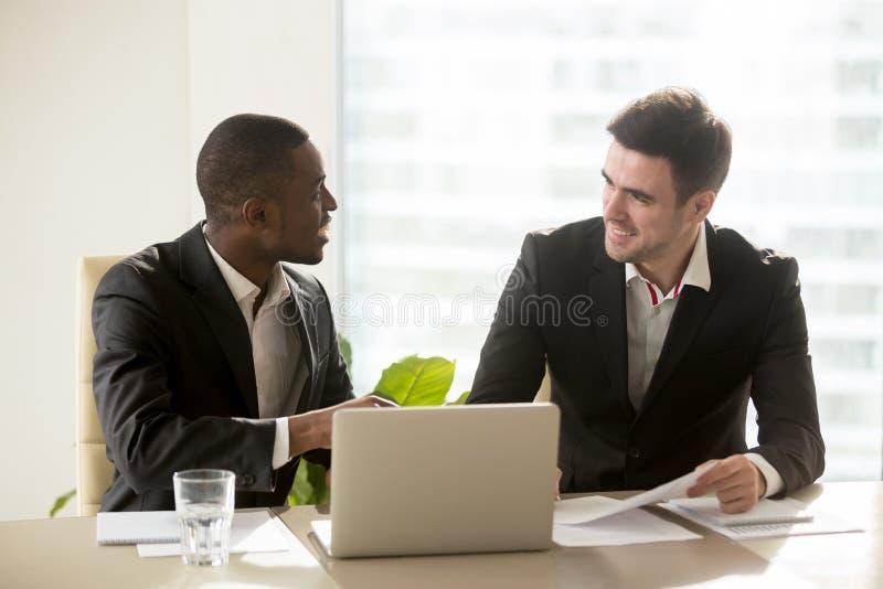 Två fulländade blandras- affärsmän som diskuterar den pro-affären fotografering för bildbyråer