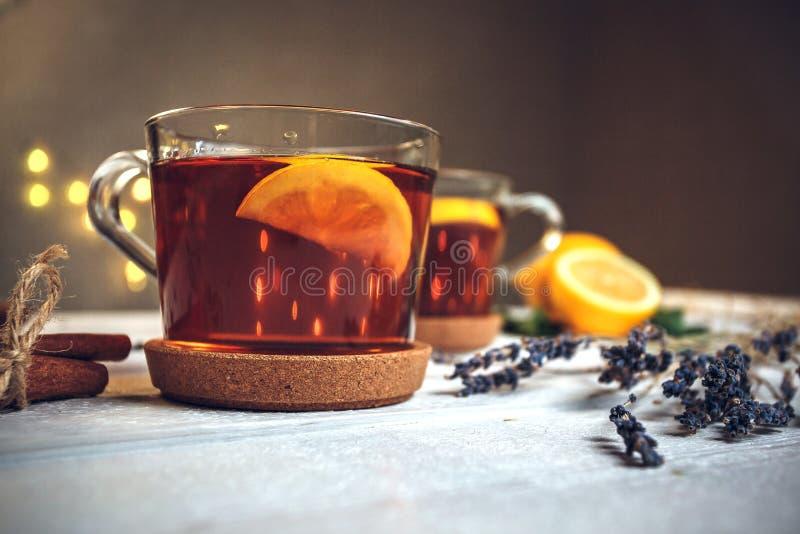 Två fulla koppar av svart te med citronen royaltyfria foton