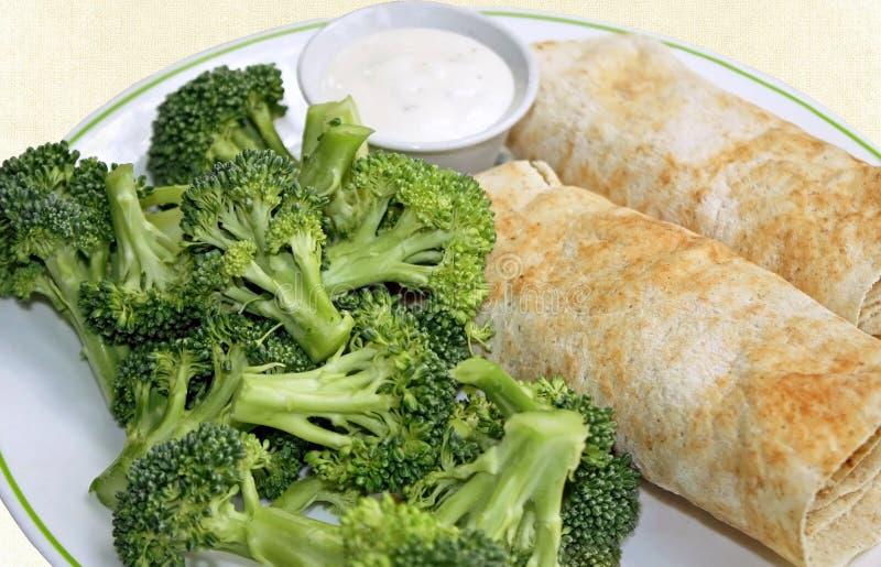 Två fyllde tortillasjalar med en sida av ny rå broccoli och en behållare av den krämiga dressingen arkivfoton