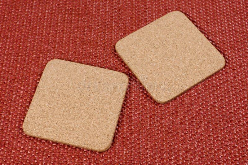 Två fyrkantiga korkställningar på en texturerad terrakottabakgrund arkivfoton