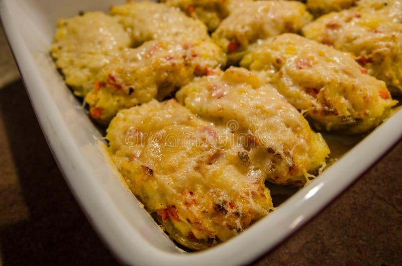 Två gånger bakade potatisar med smältt ost royaltyfri fotografi