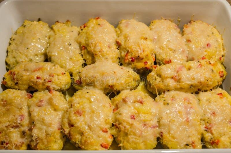 Två gånger bakade potatisar med smältt ost royaltyfria bilder