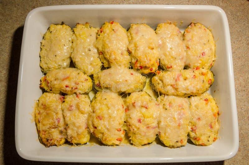 Två gånger bakade potatisar med smältt ost royaltyfri foto
