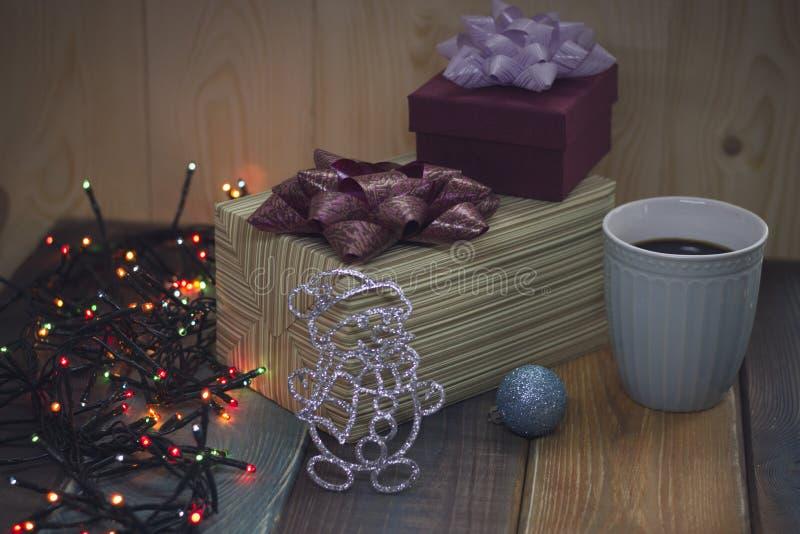 Två gåvaaskar, julleksaker, en kopp kaffe på tablenen arkivfoton