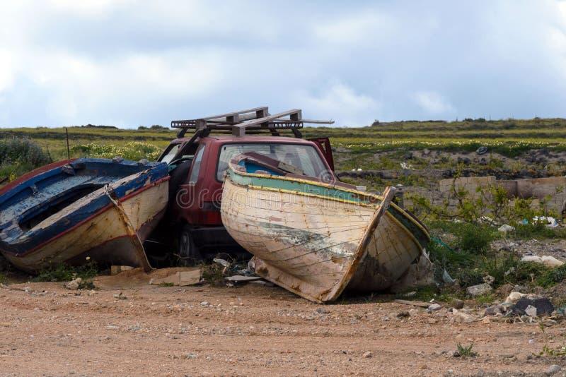 Två gamla övergav fiskebåtar och en röd skeppsbruten bil i en avskrädeförrådsplats ?vergiven saker Transport royaltyfri foto