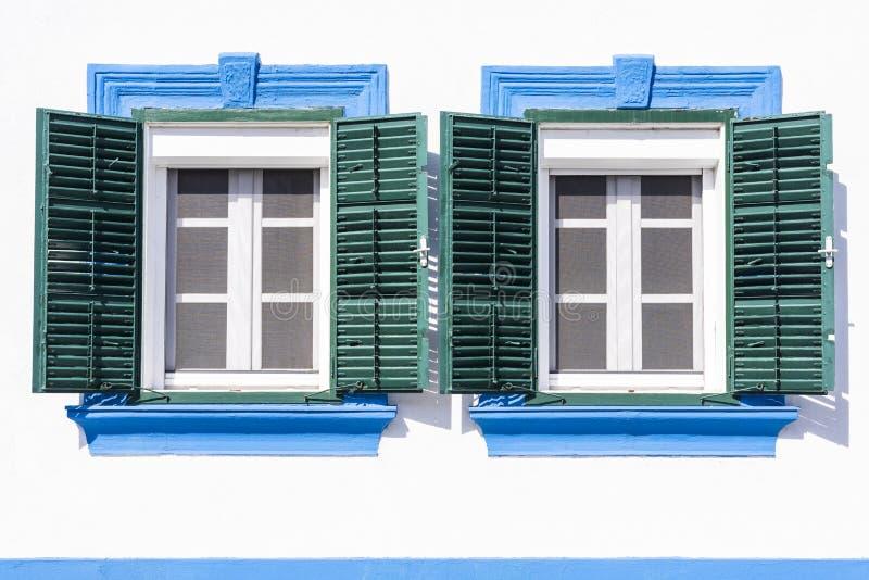 Två gamla fönster med gröna träslutare royaltyfri foto
