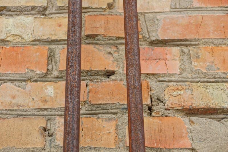 Två gamla rostiga rör på en tegelstenvägg arkivbild