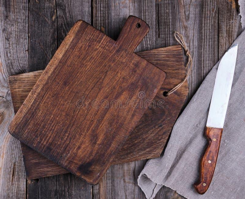 två gamla träskärbrädor och en kniv royaltyfri foto