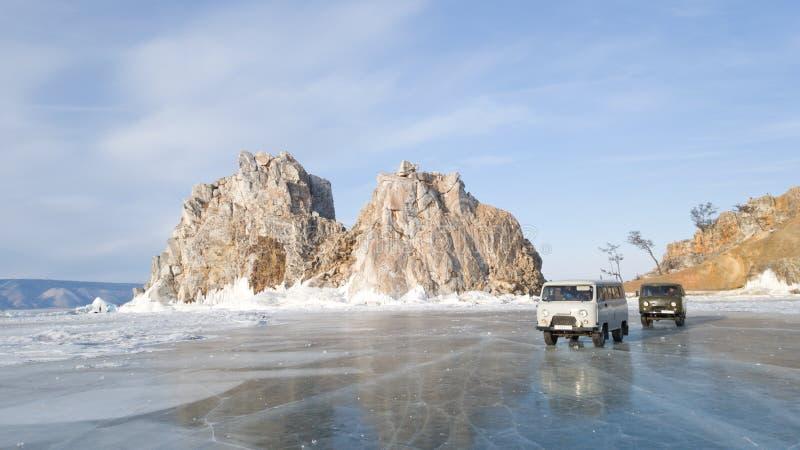 Två gamla utfärdbilar på bakgrunden av Shamanka vaggar nära den Olkhon ön Bilar är på isen av det djupfrysta Laket Baikal arkivfoton