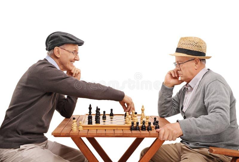 Två gamla vänner som spelar en lek av schack royaltyfri foto