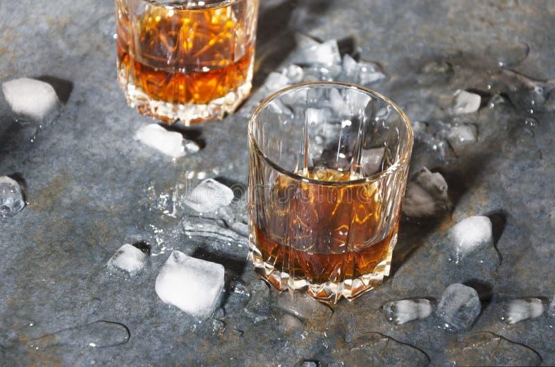 Två gammalmodiga exponeringsglas med whisky- och iskuber på stångräknare Hårt ljus och skuggor royaltyfria foton