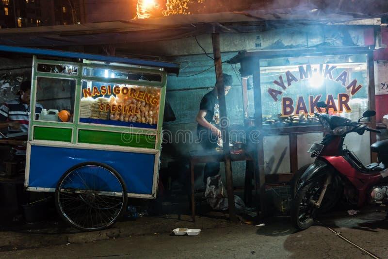 Två gatuförsäljare som säljer den nya grillade fisken och olika mellanmål royaltyfri foto