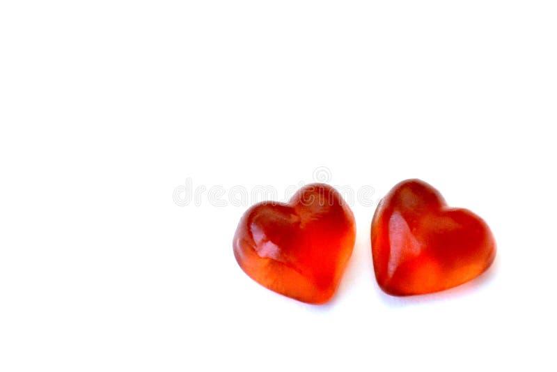 Två gelégodisar i form av röda hjärtor på en vit bakgrund med kopieringsutrymme Begreppet av förälskelse och Valentine Day royaltyfri fotografi