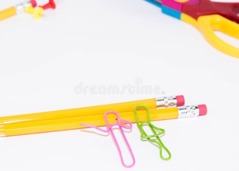 Två gemmar som talar, medan ligga på ett vitt golv och på en blyertspenna Miniatyrskolaliv och tillbaka till skolabegreppet med k arkivbild