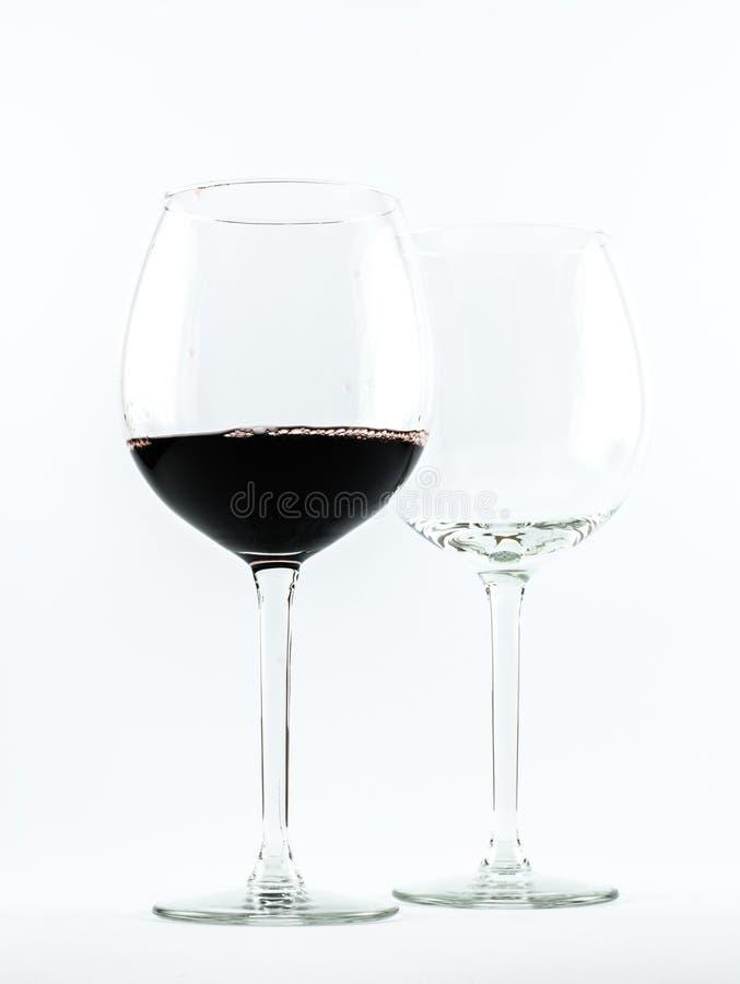 Två genomskinliga exponeringsglas - ett mycket av rött vin och annat är tomt - på en vit bakgrund royaltyfria bilder