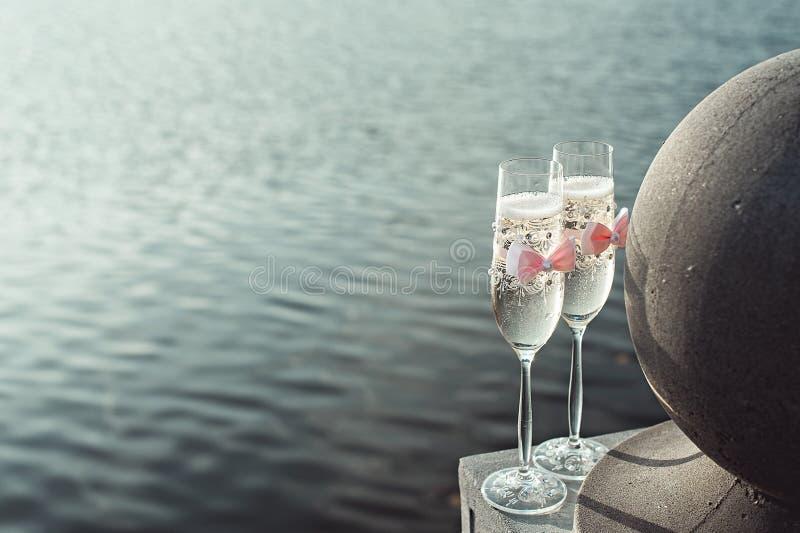 Två gifta sig champagneexponeringsglas med en pilbåge på en stenräcke Sjöpromenad på solnedgången arkivfoto
