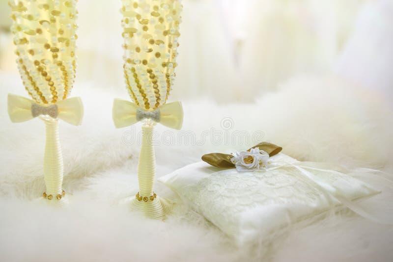 Två gifta sig exponeringsglas med champagne och kudden för cirklar på en härlig bakgrund arkivfoto