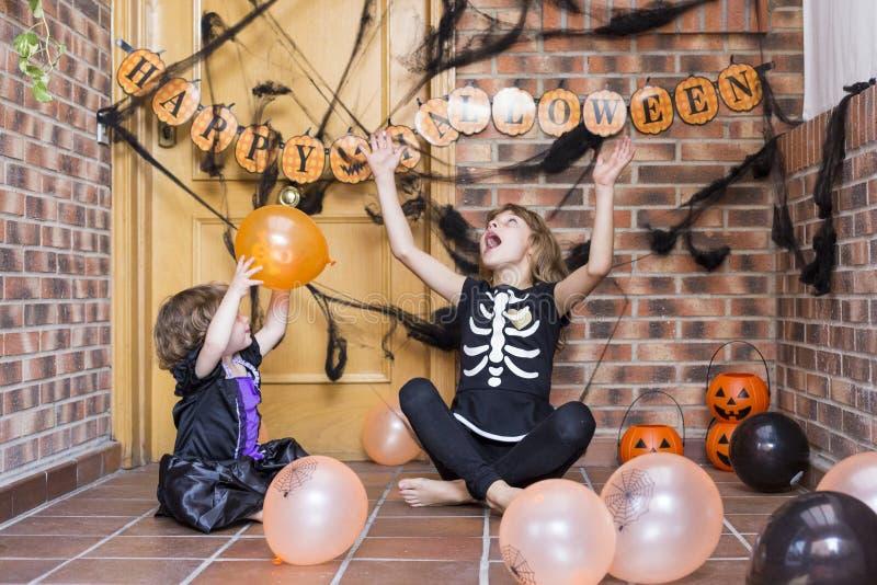 tvÃ¥ glada smÃ¥ systrar som har kul hemma och som har halloween-kostymer och leker med ballonger. behandla trick. inomhus fotografering för bildbyråer
