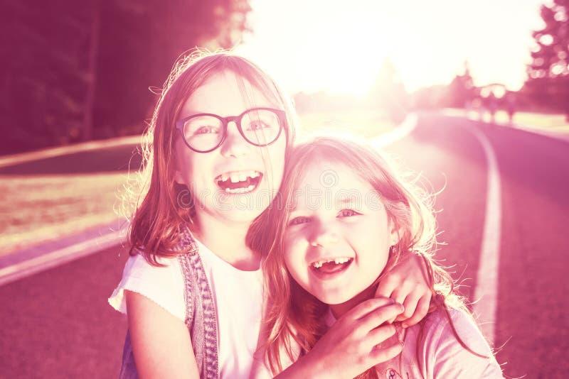 Två glade flickor som kramar och ler mot solnedgången royaltyfria bilder