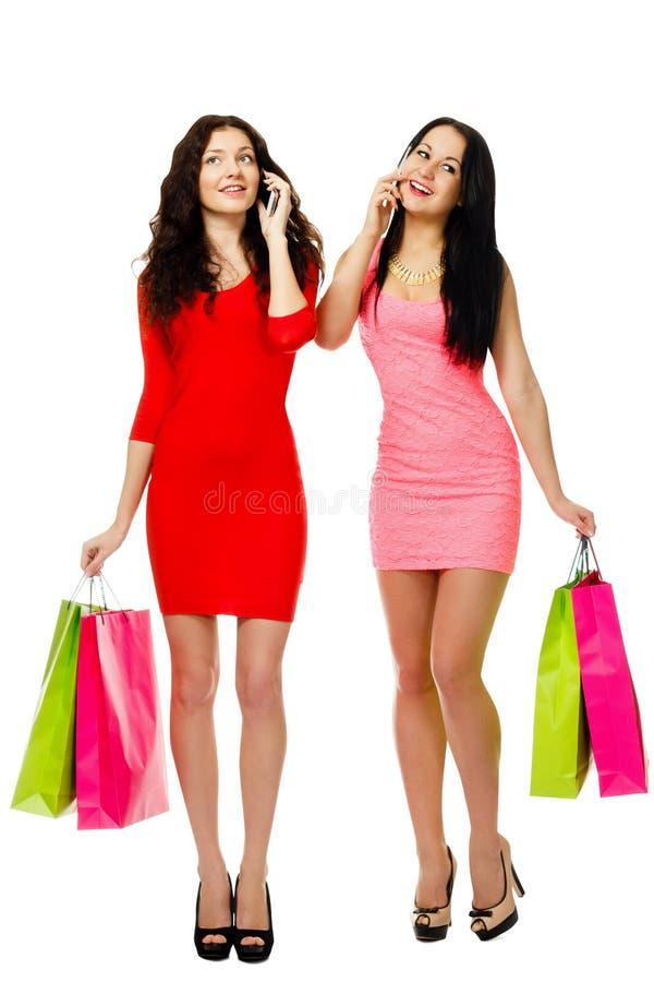 Två glade kvinnor för ung shopping som talar vid telefonen royaltyfri foto