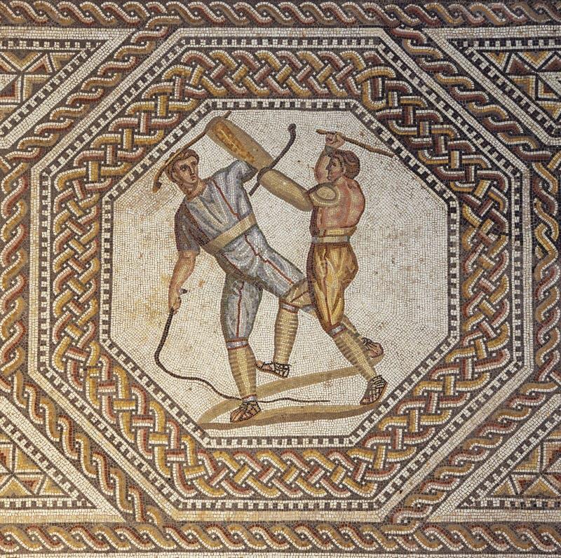Två gladiatorer som slåss med, piskar och en klubba arkivbild