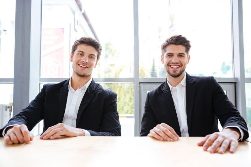 Två gladlynta affärsmän som i regeringsställning sitter på tabellen royaltyfria foton