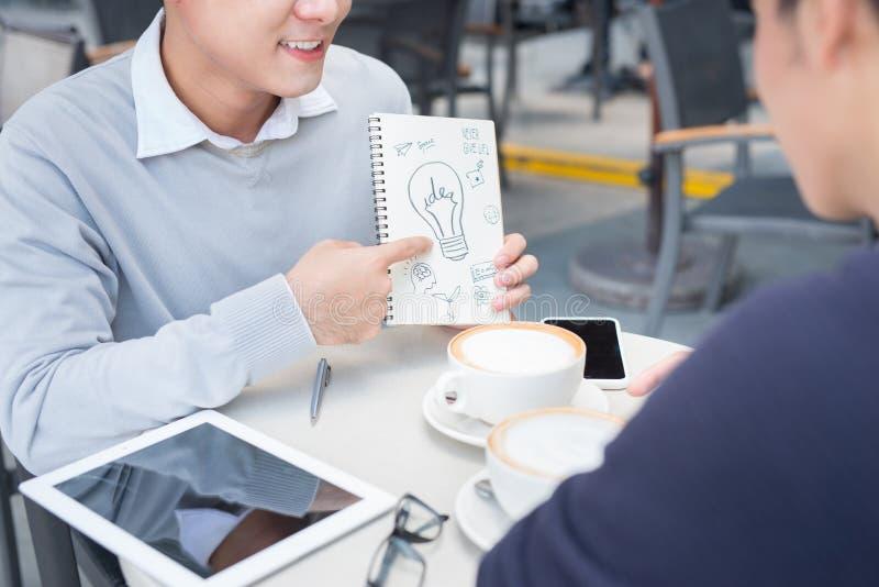 Två gladlynta asiatiska affärspersoner som diskuterar med dokument arkivbild