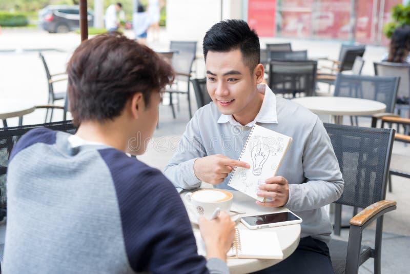 Två gladlynta asiatiska affärspersoner som diskuterar med dokument royaltyfri bild