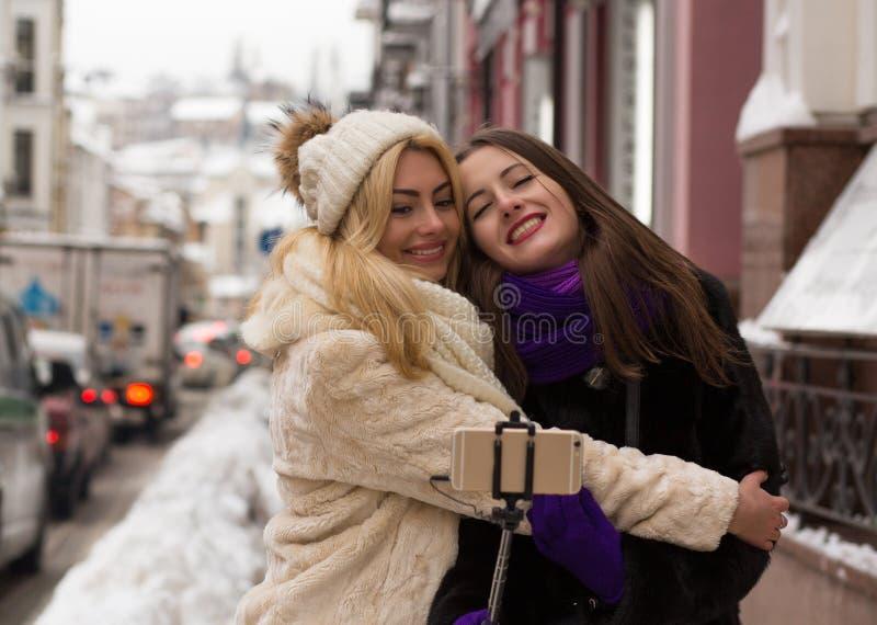 Två gladlynta flickavänner som tar en självstående på gatan fotografering för bildbyråer