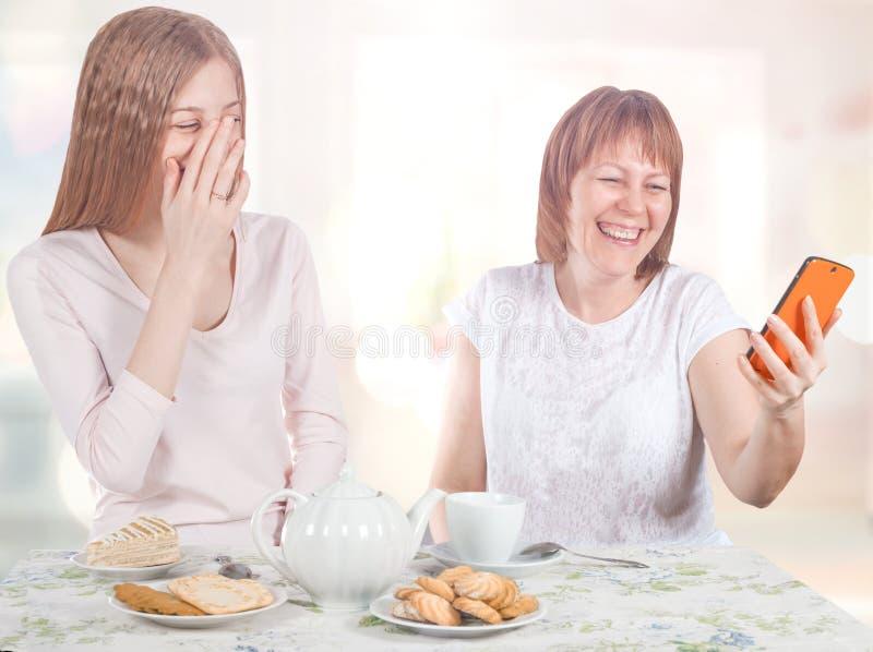 Två gladlynta flickvänner ser fotoet i smartphonen royaltyfri foto